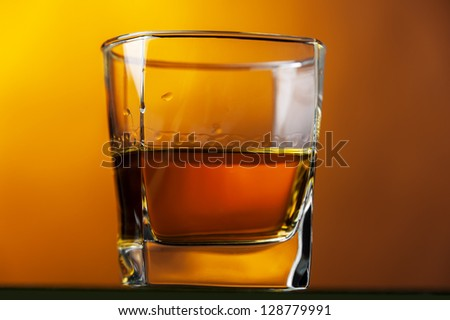 a glass of whiskey at warm background