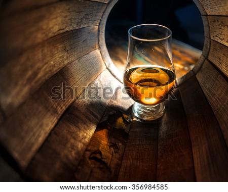 A glass of whiskey in oak barrels - stock photo