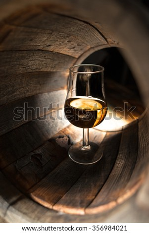 A glass of whiskey on a background of oak barrels - stock photo