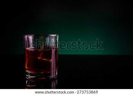 A glass of whiskey  or rum, with green light and copy space