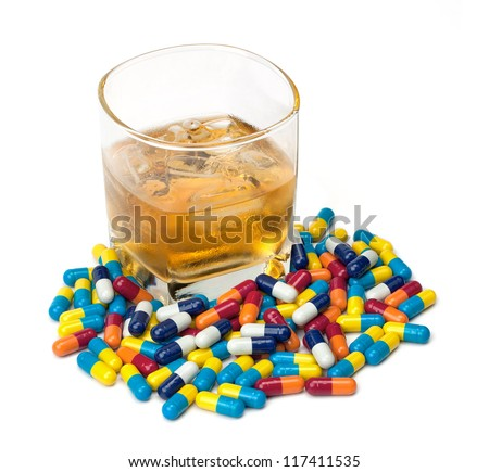A glass of whiskey surrounded by pills isolated on white. - stock photo