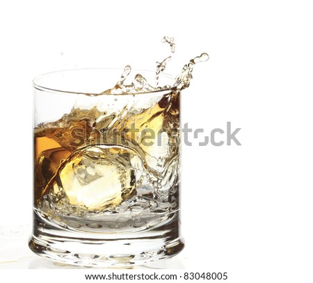 A Glass of whisky with ice cube splash isolated on white - stock photo