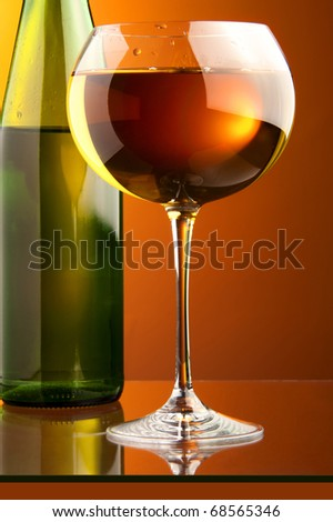 a glass of white wine and a detail of a green bottle