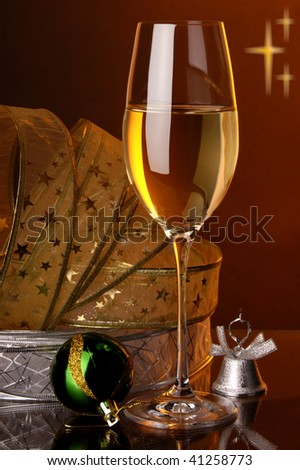 a glass of white wine and christmas decoration - stock photo