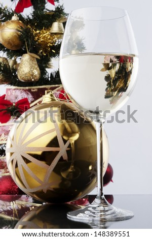 a glass of white wine and Christmas decoration against Christmas tree at background
