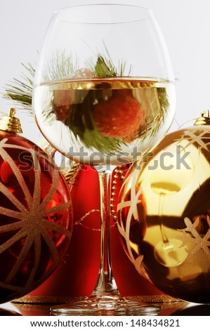 a glass of white wine and Christmas decoration against white background  - stock photo