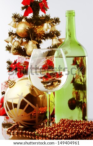 a glass of white wine and green wine bottle and Christmas tree as a background and decoration  - stock photo