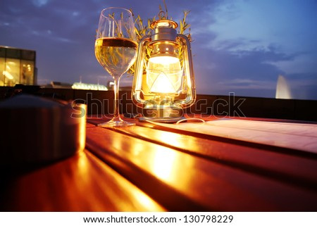 A glass of white wine besides a lantern. - stock photo