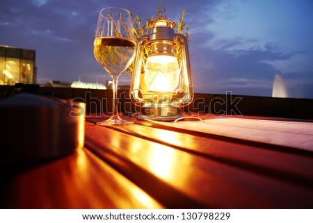A glass of white wine besides a lantern. - stock photo