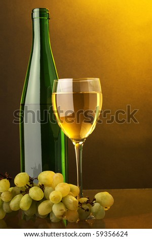 a glass of white wine bottle and green grape