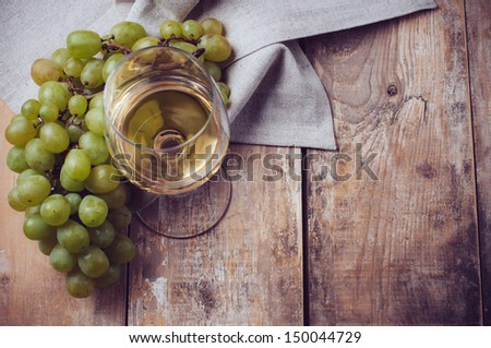 A glass of white wine, grapes, coarse linen cloth on a wooden board, closeup - stock photo