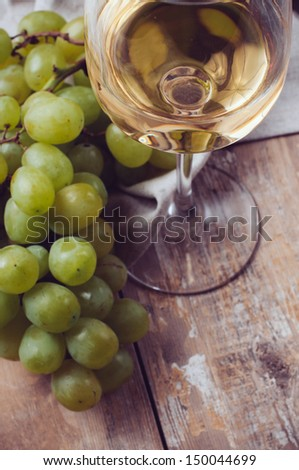A glass of white wine, grapes, coarse linen cloth on a wooden board, extremely closeup