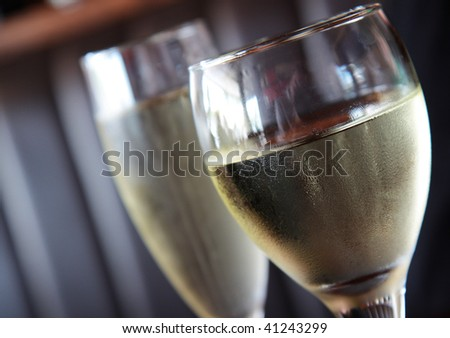 A glass of white wine, with a glass of champagne in the background.