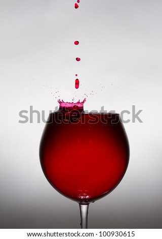 A glass of wine and a drop falling into it. From the drop of fly spray. - stock photo