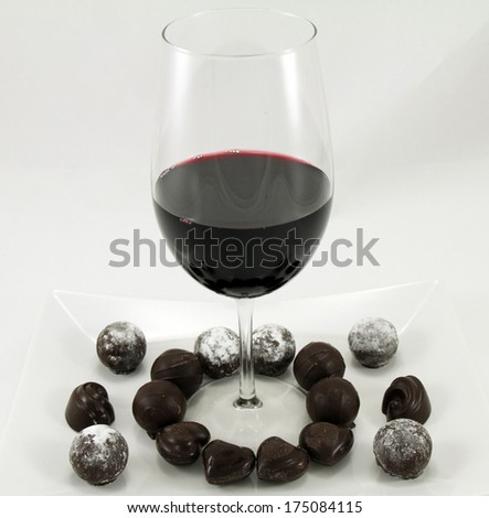 A glass of wine and assortment of chocolates on a white plate. - stock photo