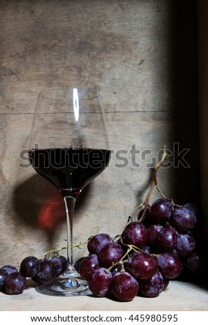 a glass of wine and bunch of grapes in a wooden box