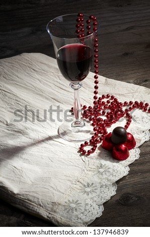 A glass of wine and chocolate pralines - stock photo