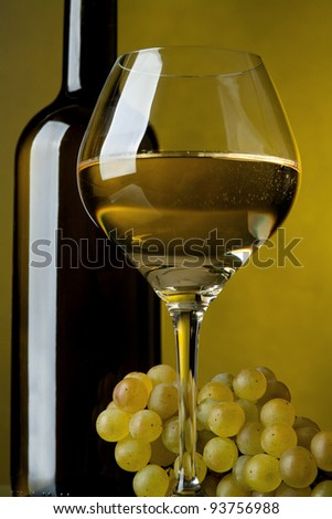 A glass of wine, bottle and grapes on a yellow background - stock photo