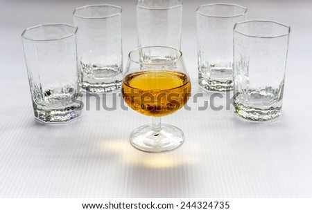 A glass of wine surround by empty water glasses.  Standout concept. - stock photo