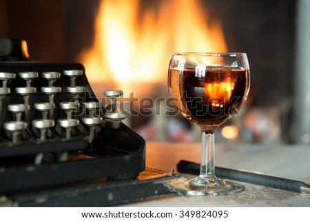 a glass of wine, typewriter and a fireplace - stock photo