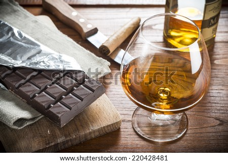A Glass on Cognac, Cuban Cigar and Chocolat on wood background  - stock photo