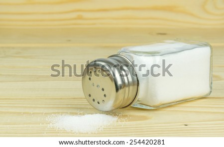 A glass salt shaker with metal lid and spilled salt  - stock photo