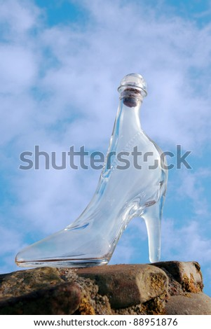 a glass slipper on a stone surface with a cloudy blue sky background - stock photo