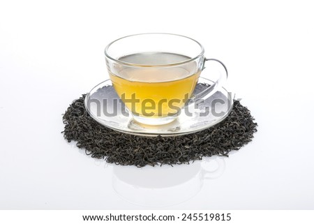 A glass tea cup with tea and leaf(leaves) isolated white at the studio. - stock photo