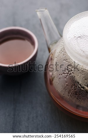 A Glass Teapot containing Freshly brewed Tea and Cup.