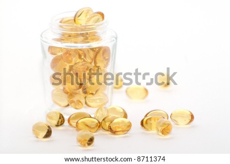 A glass with golden pills - stock photo