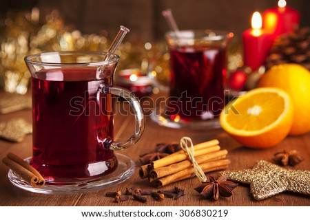A glass with mulled wine or glühwein on a rustic table with ingredients and Christmas decorations. - stock photo