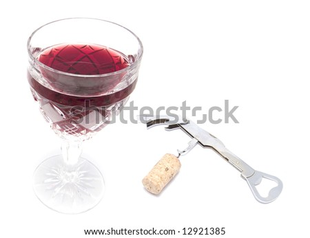 a glass with red wine and an opener wioth a cork - stock photo
