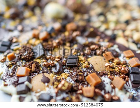 A glittery slab of melted chocolate, fudge and coffee beans close up selective focus.