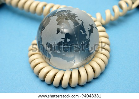 A globe and phone cord represent global communications. - stock photo