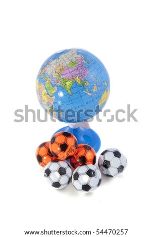 A globe and some footballs on a white background. - stock photo