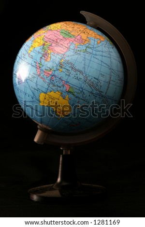 A globe lit from the left with a dark background