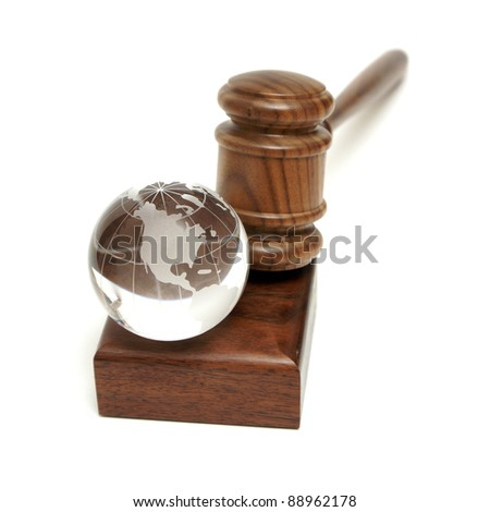 A globe rests near a gavel for worldly concepts like global auctions and world order.