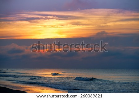 A glorious, colorful sunrise sky over the Atlantic Ocean is seen at Emerald Isle, North Carolina. - stock photo
