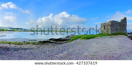 A glorious panorama view of the beach and ruined castle at Ballinskelligs with blue sky and white clouds, The Ring of Kerry, County Kerry, Ireland