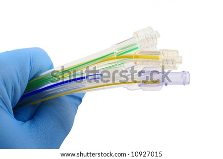 a gloved hand grasping striped medical tubing with fittings - stock photo