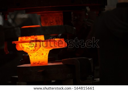 a glowing iron ingot into the press