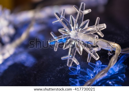 A glowing white xmass star at blue reflective background - stock photo