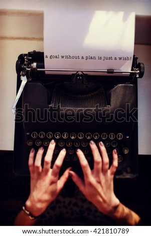 A goal without a plan is just a wish message on a white background against womans hand typing on typewriter - stock photo