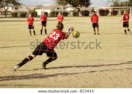A goalie practices for a girl's soccer game. - stock photo