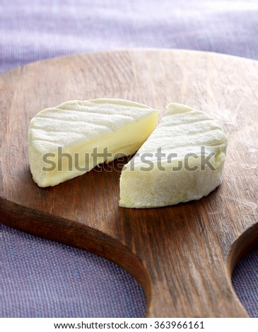 A goat cheese cut in half on a cutting board