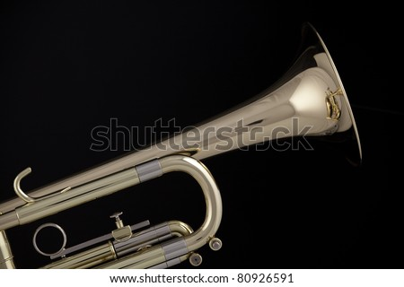 A gold and brass trumpet or cornet isolated against a black background. - stock photo