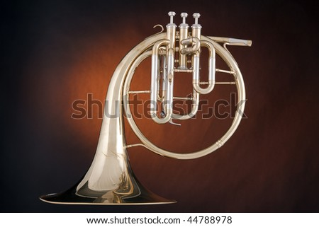 A gold antique peck-horn or French horn isolated against a spotlight gold background. - stock photo