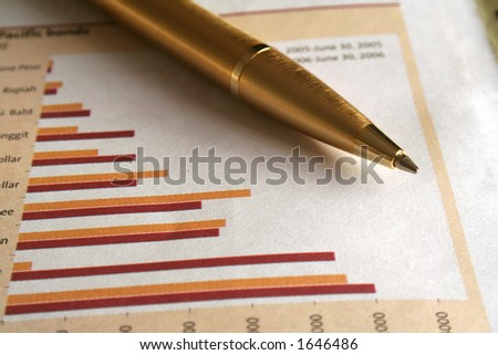 A gold ballpoint pen on the business page of the newspaper. - stock photo