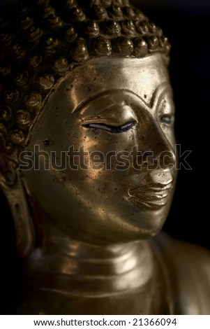 A gold Buddha in a dimly lit room.
