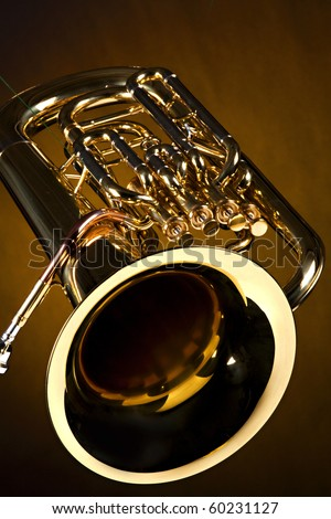 A gold color brass tuba euphonium isolated against a spotlight gold background in the vertical format. - stock photo